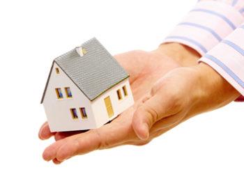 Hände halten kleines Haus